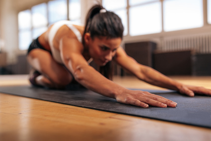 Woman doing stretching workout on fitness mat, focus on hands, fitness female performing yoga on exercise mat at gym.